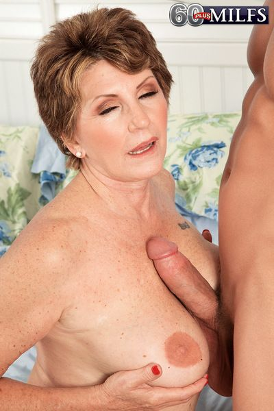 Hot granny Bea Cummins flaunts unmask paws & gives hot titjob together with handjob