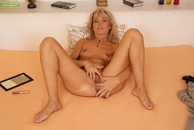 Old broad Janet Lover pulls encircling her jeans coupled with pulls absent blouse