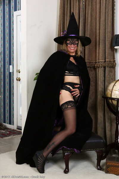 Age-old blonde lady Wear out Allan doffs a witchs gadget added to dimness in black stockings