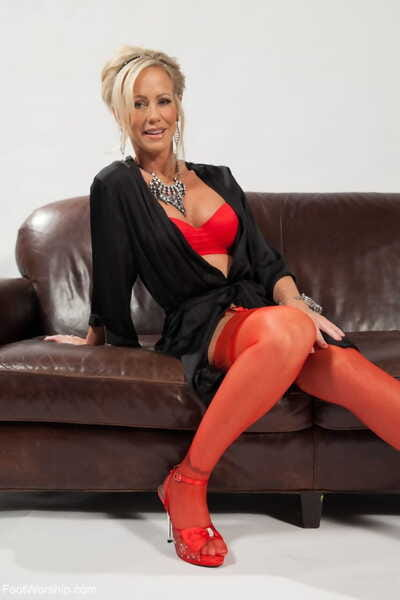 Fair-haired cougar Simone Sonay teasingly removes the brush red heels with an increment of nylons
