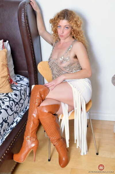 Curly-haired Leona demonstrates unshaved armpits and wooden-headed pussy in sexy boots