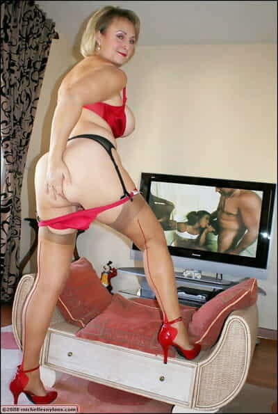 Beamy tow-haired adult down stockings and high heels watching porn and masturbating