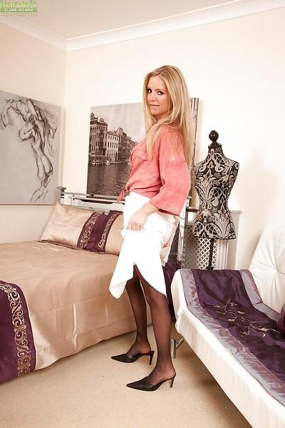 Stunning MILF in stockings stripping and showcasing her trimmed muff