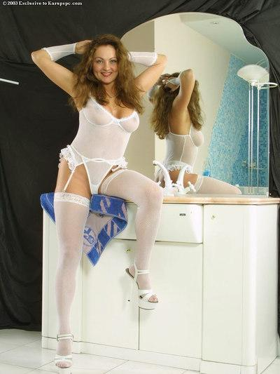 Sexy redhead Alena is having her new white stockings on
