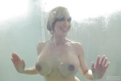 Buxom blonde pornstar Brandi Love pressing big wet tits up against glass