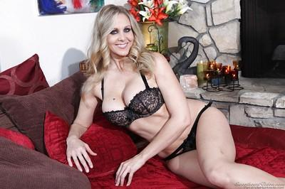 Blonde babe model Julia Ann posing in black bra and panties on couch