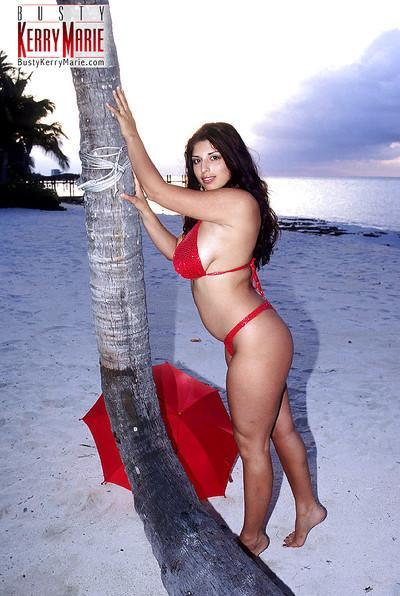 Brunette pornstar Kerry Marie unleashing massive melons outdoors on beach