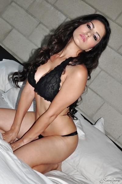 Milf babe Sunny Leone is posing in her stunning black lingerie