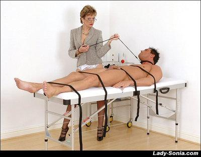 Bottomless mature femdom in glasses jerking a bound guy