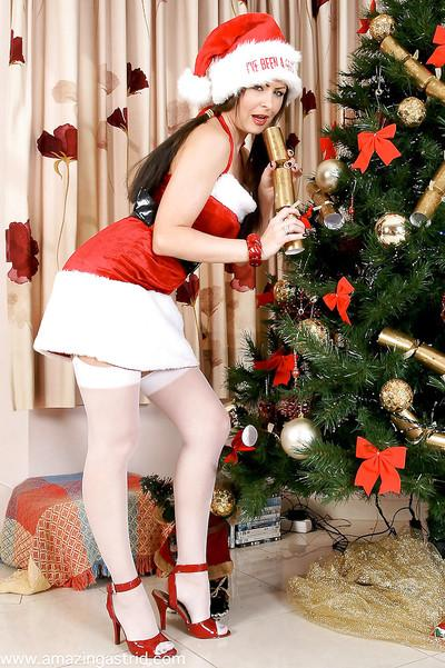 Brunette lady in pigtails striking sexy poses in Santa outfit and stockings