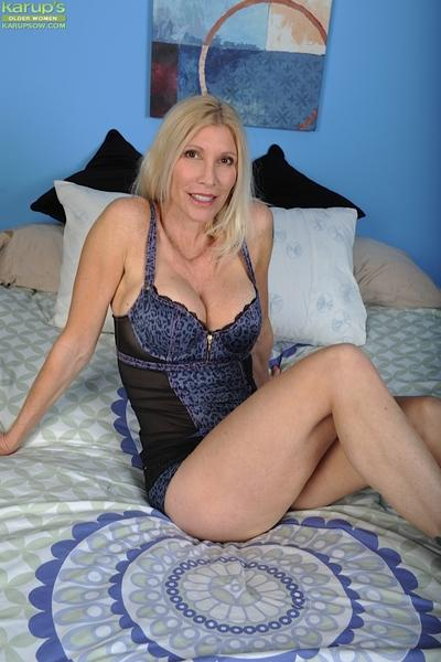 Mature blonde woman Cameo removing lingerie to pose nude on bed