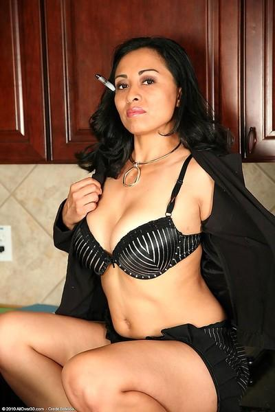 Big breasted mature latina secretary takes off her black lingerie and shows her smoking body.