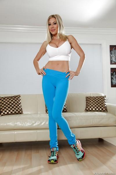 Busty blonde bodybuilder Puma Swede posing in sports bra and yoga pants