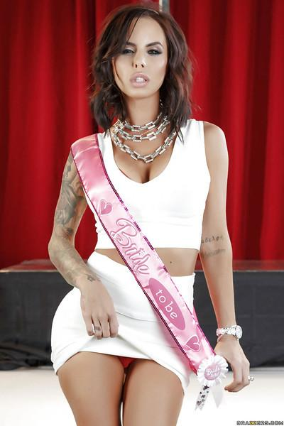 Tattooed MILF babe Brandy Aniston posing fully clothed in white skirt
