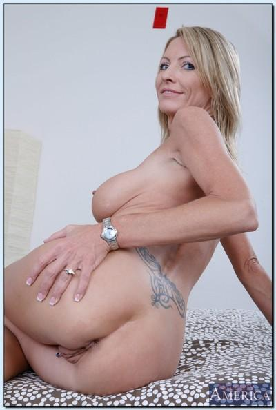 Sexy MILF Emma Starr getting naked and exposing her pierced slit in close up
