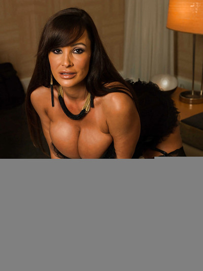 Milf Lisa Ann in stockings spreading her legs while laying on a bed