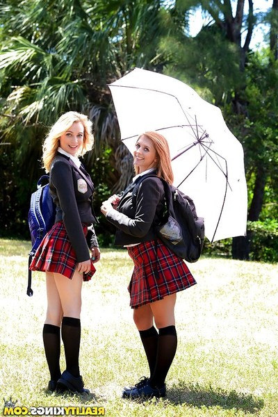 Youthful schoolgirls Cali Sparks and Kelly Greene tongue mouth to mouth outdoors