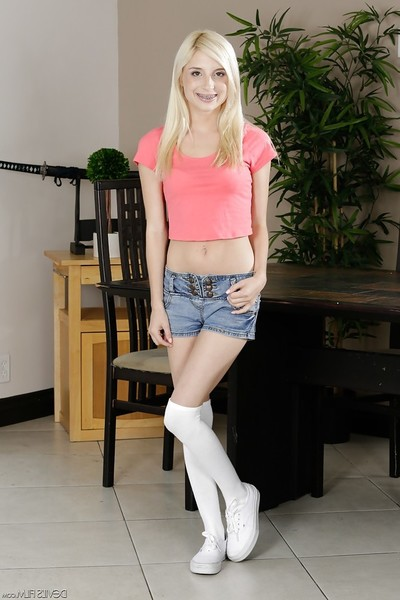 Youthful blond Piper Perri flashing famous braces adorned smile in socks