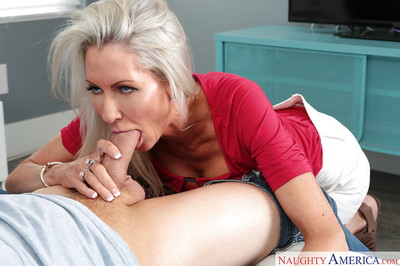 Grey haired cougar Emma Starr kisses a younger male in advance of giving head