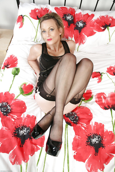 Unconventional MILF Betsy Blue posing on her couch in high heels and nylons