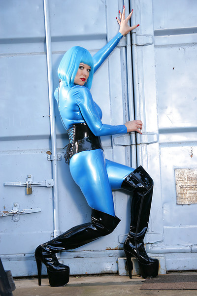 Decadent dear in latex garments and ebon boots posing outdoor