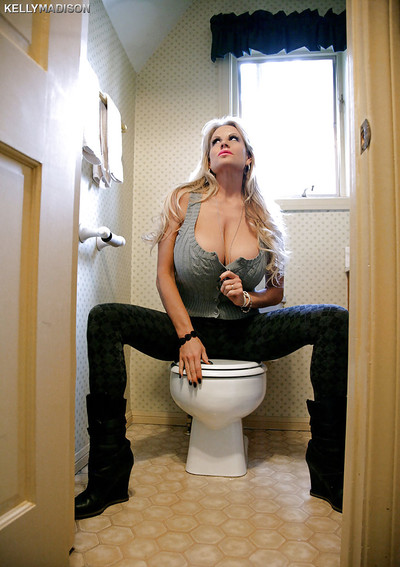 Milf blondie Kelly Madison is undressing her inflexible shirt in a washroom