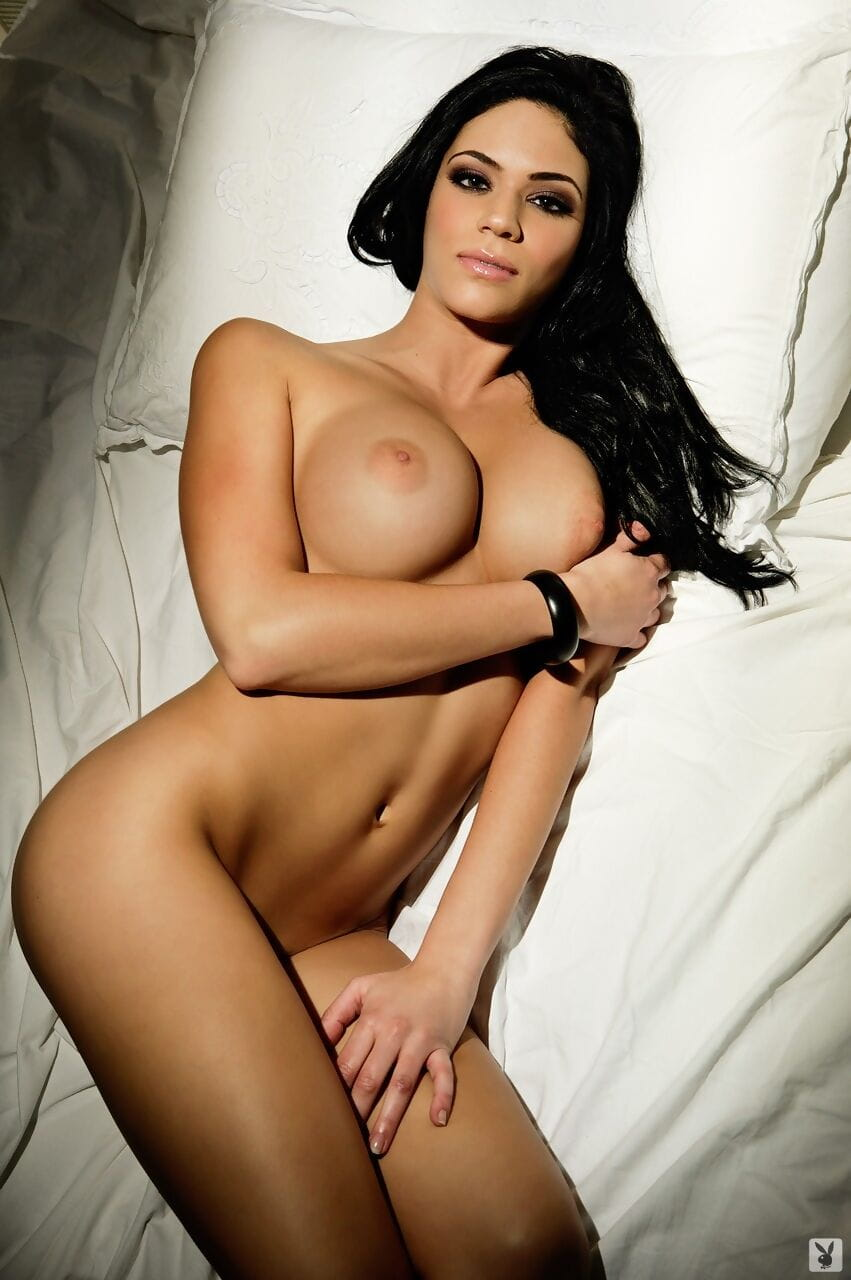 Nice-looking hottie Melany Denyse holds her massive silicone front bumpers although posing in daybed
