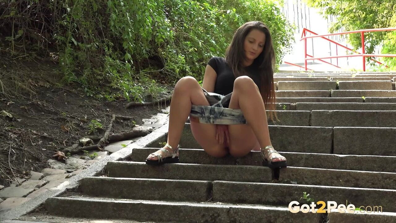 Pretty dark brown Nicolette Noir pauses on the park steps for a crave damp pee