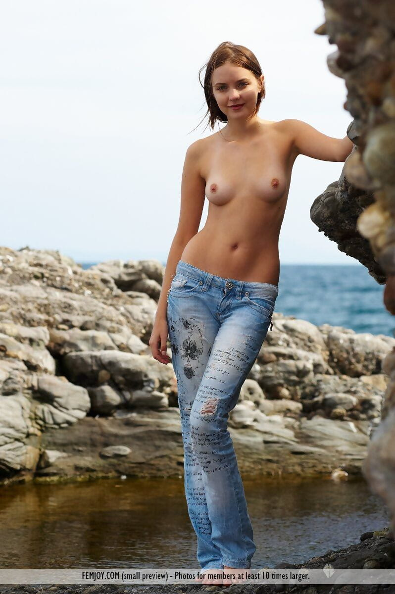 Topless youthful takes off blue jeans to pose her fascinating body on rocks by ocean