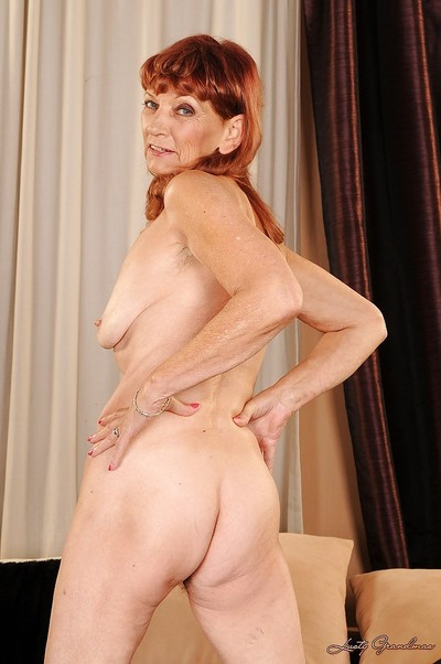 Redhead ripened on high heels stripping and exposing her bushy cunt