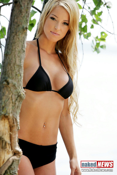 Blonde model slips on her sexy bikini and sun bathes on the beach
