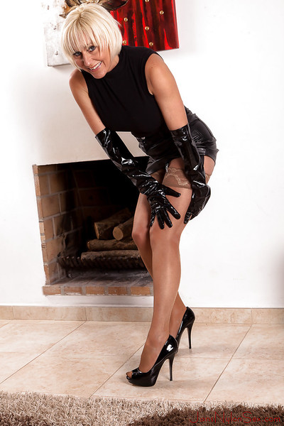 Short haired granny dame Jan Burton posing solo in long black latex gloves