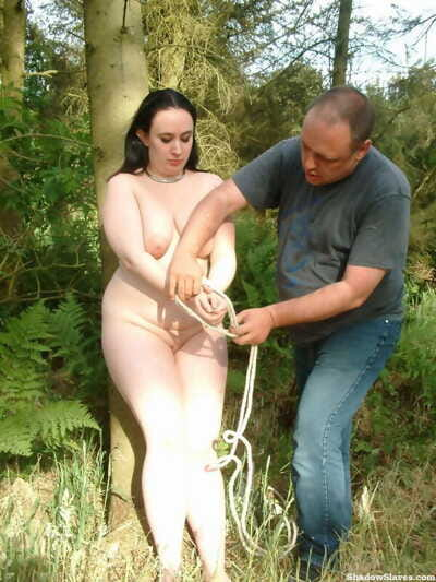 Chubby female has garments pegs fastened to breasts while tied in nature