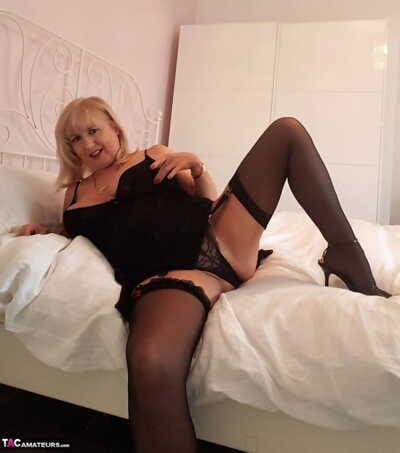 Thick older woman Lornablu slides sheer panties aside to display her skinhead fur pie