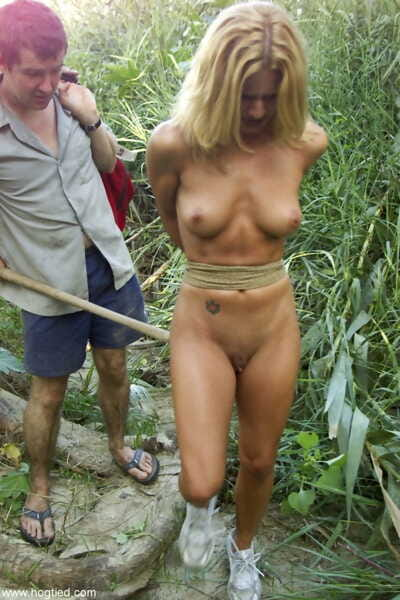 Skinny blonde Jenni Lee is tied to a tree in woods and tit tortured