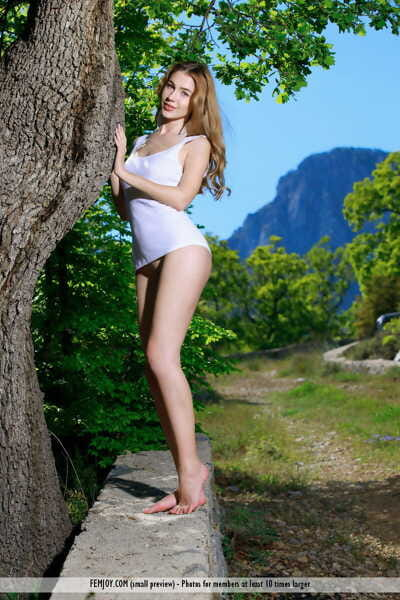 Bare legged amateur Xana D removes container dominant for nude positions in front of a tree