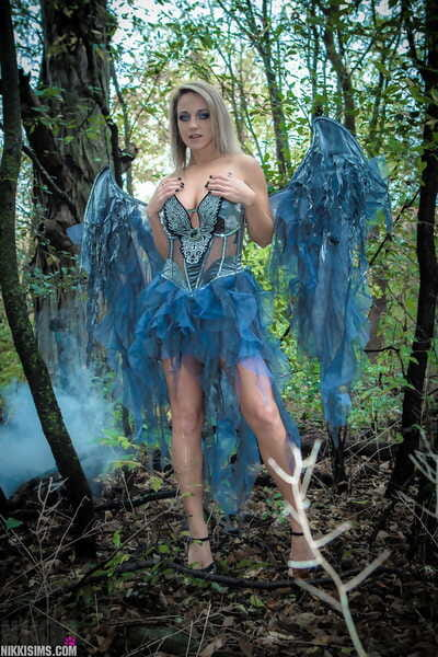 Fairy-haired cosplay lass Nikki Sims doffs her wings and wisp to pose in a strap