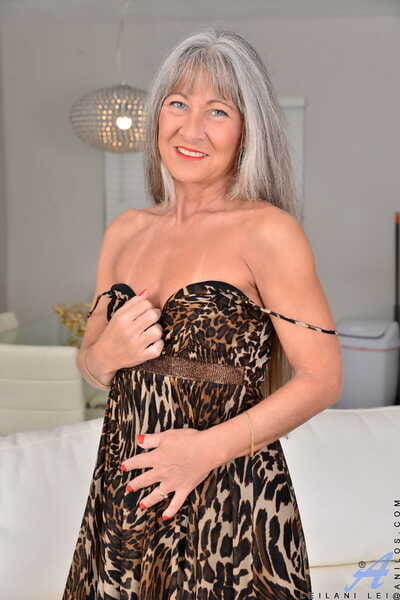 Grey haired adult Leilani Lei shows her diminutive tits with tan lines & her twat