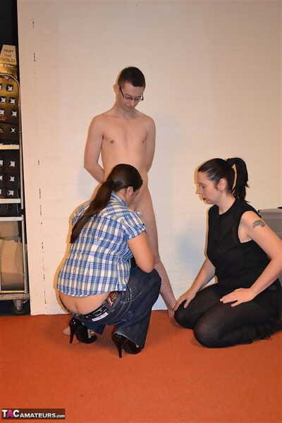 Covered dykes force a naked male slave to suck on a  cock