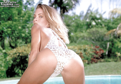 Chesty blond pornstar Tiffany Towers posing beside pool for solo angel shoot