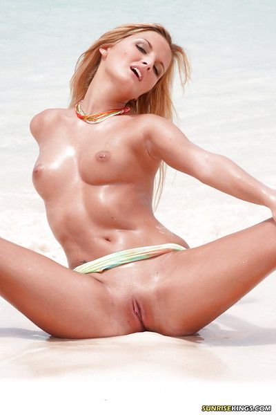 Golden-haired pornstar showing off her hard booty and boobs on the beach