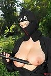 Ninja attired dear Shione Cooper freeing large natural tits in the forest